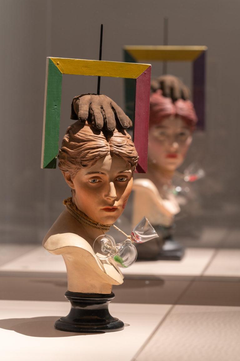 skulptur. kvindetorso med handkse på hovedet og ramme rundt om hovedet, penis på den ene kind