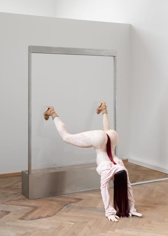 skulptur af kvinde der twerker på hovedet med benene i luften mens hun bløder fra underlivet
