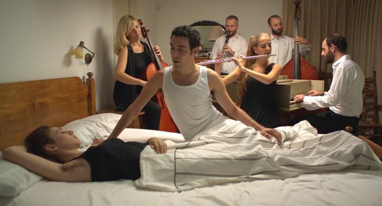 film still: klassisk orkester der spiller foran kvinde i hvid seng