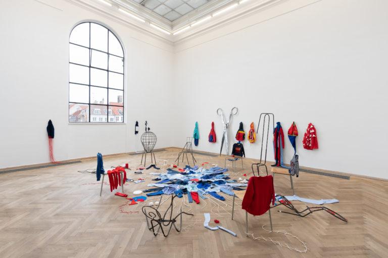 installation: stole i en rundkreds. i midten: gulvtæppe lavet af sammensyede skjorter. på væggen hænger fterladte rygsække og trøjer