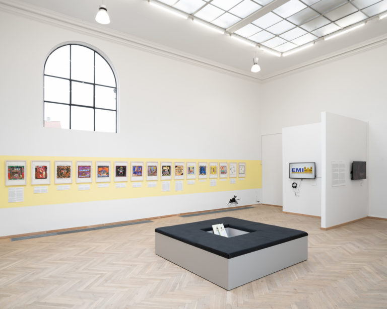 installationsbillede af mange små værker der hænger på væg