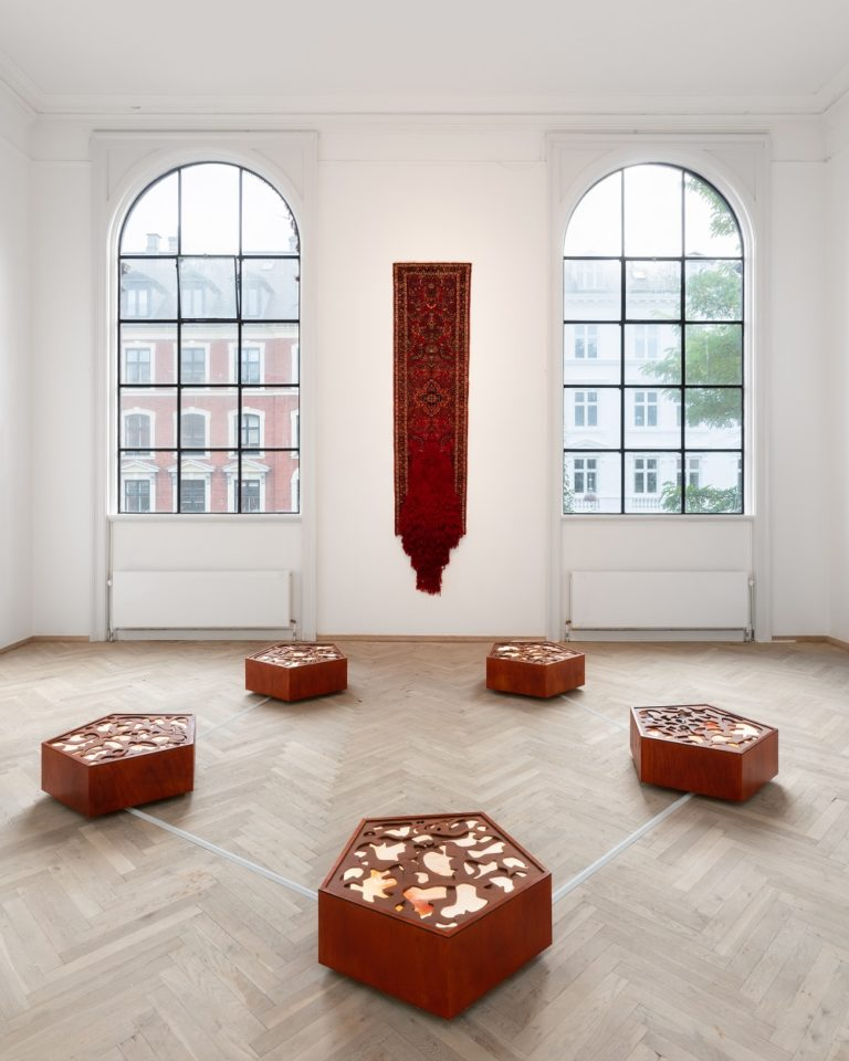 Et rødt tæppe hænger på væggen, fem træskulpturer står på gulvet i en pentagonform.