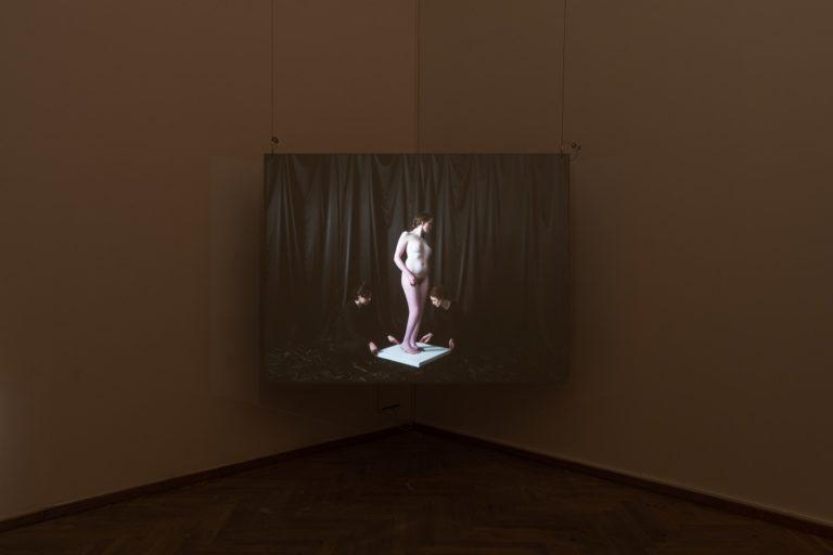 Still fra film af nøgen kvinde der står i samme positur som en antik skulptur.