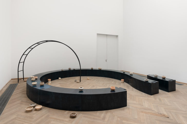 Stor ovalformet skulpturinstallation i sort.