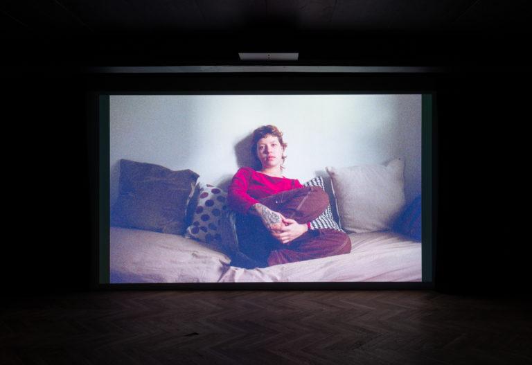 Still fra film af kvinde der sidder i sin seng