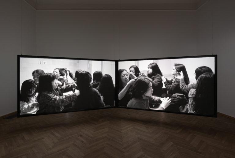 to store videoskærme der viser kvinder der fletter hinandens hår
