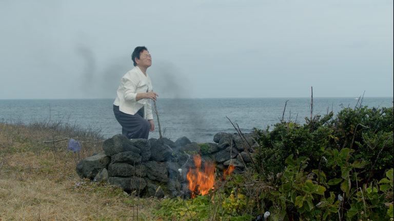 shamanistisk ritual udført af kvinde ved bål på stranden