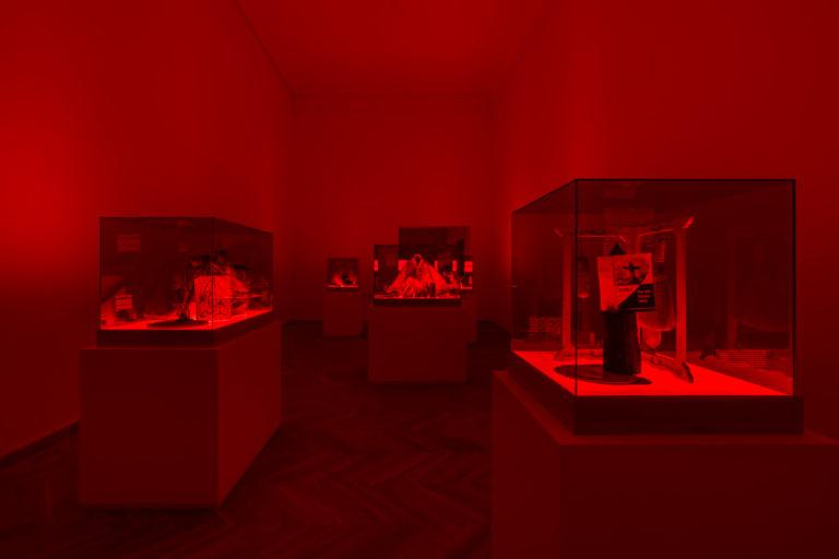 installation: rødt rum med rødt lys. glasmontrer med fundne objekter