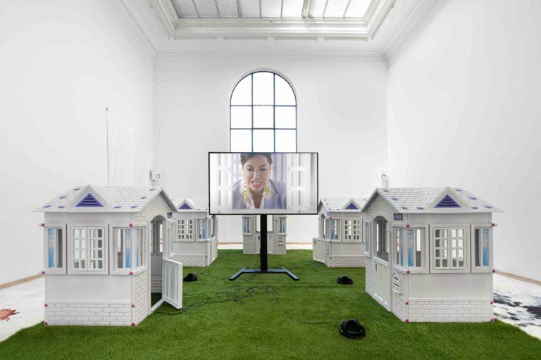 videoinstallation: skærm placeret på grønt græs, fire små legehuse rundt om