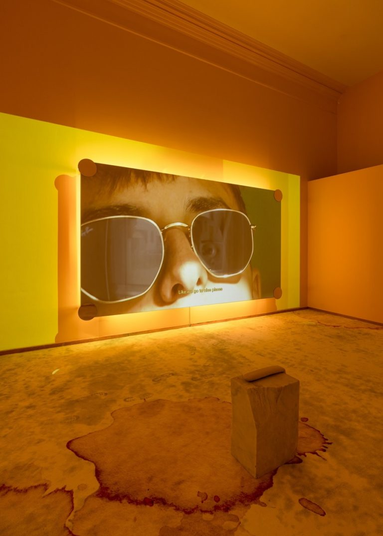 film still: closeup af ansigt med solbriller. rummet er belyst med gult lys. blodpletter og andre plamager på gulvet.