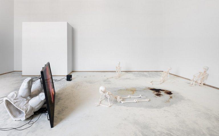 Videoinstallation: Skeletter kigger på videoskærmen, blod og kaffepletter på gulvet.