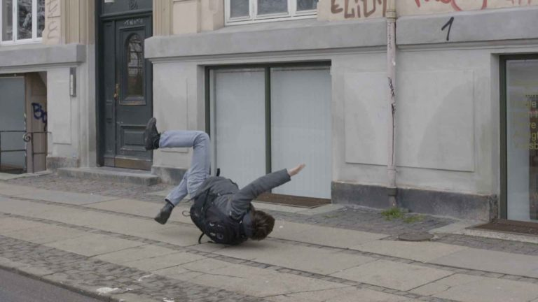 Still fra film af mand der falder på gaden.