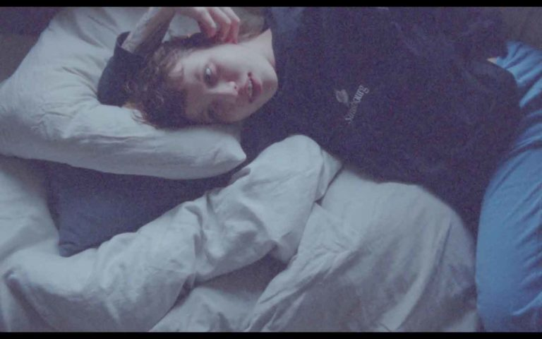 Still fra film af kvinde der ligger i en seng.
